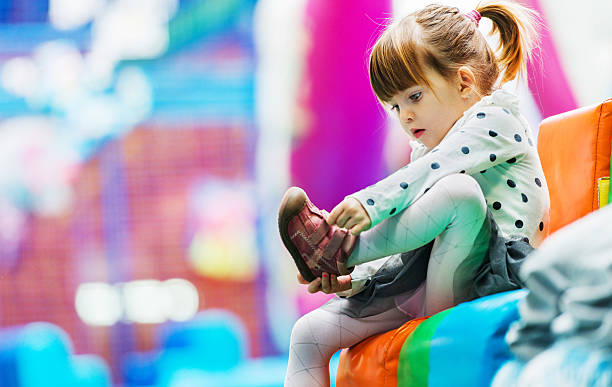 I'm a big girl! Little girl taking her shoes off in the playroom. undressing stock pictures, royalty-free photos & images