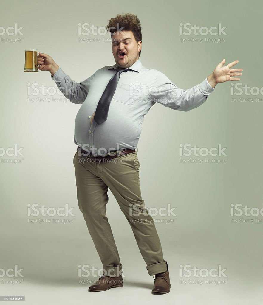 I'm a party animal! Shot of an overweight man celebrating while holding a pint of beer 20-29 Years Stock Photo