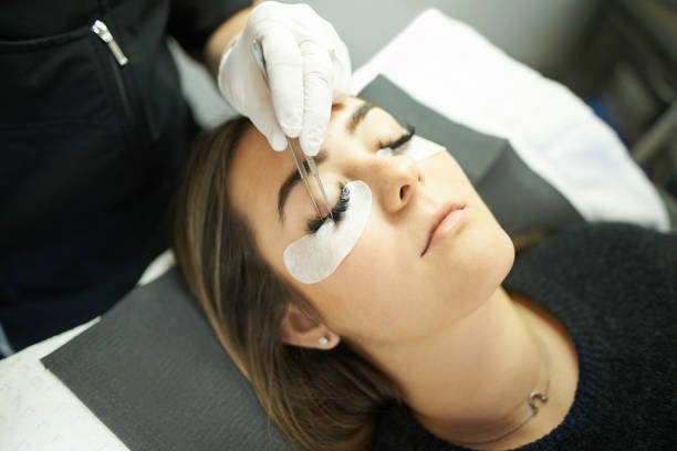 I'm achieving those perfect lash goals Cropped shot of a young woman getting eyelash extensions false eyelash stock pictures, royalty-free photos & images