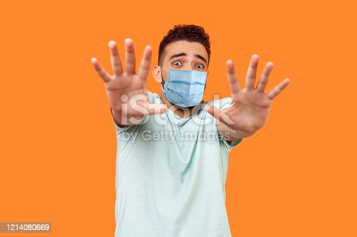 istock I'm afraid! Portrait of scared terrified man with medical mask in white t-shirt making frightened gesture with raised hands, panic attack concept. 1214080669