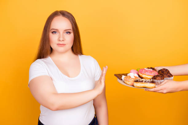 I'm against eating products containing fat! Will-powered woman wearing white tshirt is refusing to consume tasty delicious sweets on a plate, isolated on bright yellow background I'm against eating products containing fat! Will-powered woman wearing white tshirt is refusing to consume tasty delicious sweets on a plate, isolated on bright yellow background temptation stock pictures, royalty-free photos & images