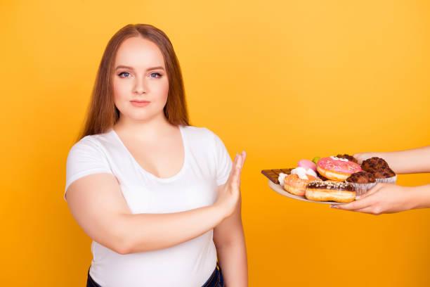 ich bin gegen asbesthaltigen fett essen! willen betriebene frau trägt weißes tshirt weigert sich, schmackhafte leckere süßigkeiten auf einem teller, auf hellen gelben hintergrund isoliert zu verbrauchen - fett nährstoff stock-fotos und bilder