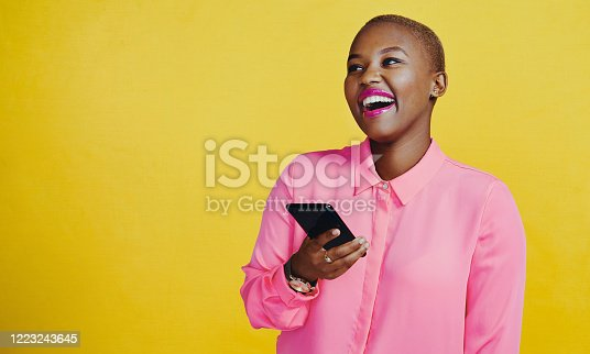 Cropped shot of an attractive young woman using her cellphone in studio against a yellow background