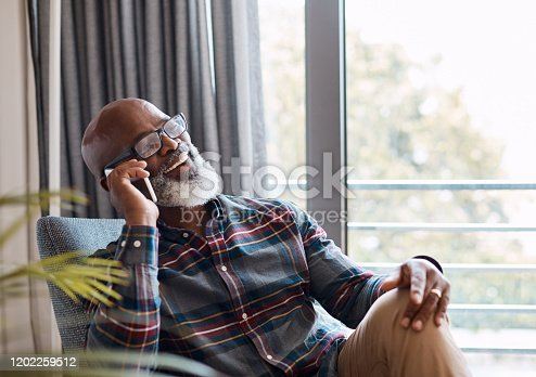 Shot of a mature man talking on a cellphone while relaxing on a sofa at home