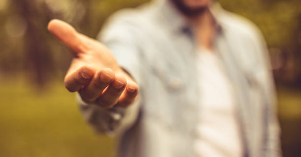 I'm always here to provide support. I'm always here to provide support. Young man in standing in park stretches his hand. Focus is on hand. Close up. assistance stock pictures, royalty-free photos & images