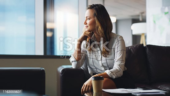 Cropped shot of a businesswoman looking thoughtful while sitting in a modern office