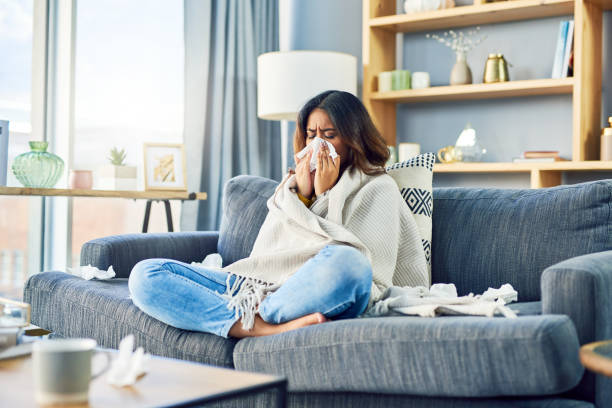 I'm always sick on the wrong days! Shot of a young woman blowing her nose while sitting at home cold virus stock pictures, royalty-free photos & images
