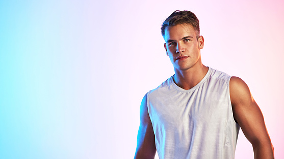 Studio portrait of a handsome young male athlete posing against a multi-coloured background