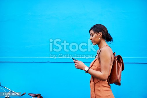 Shot of an attractive young woman using a cellphone while traveling with her bicycle against a blue background outdoors
