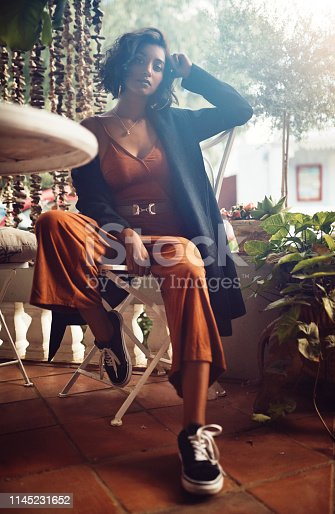 Shot of a fashionably dressed woman sitting outside