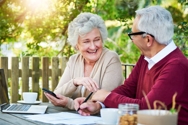I'm extremely proud of us Cropped shot of a senior couple going over their finances while sitting outside on the veranda pension stock pictures, royalty-free photos & images