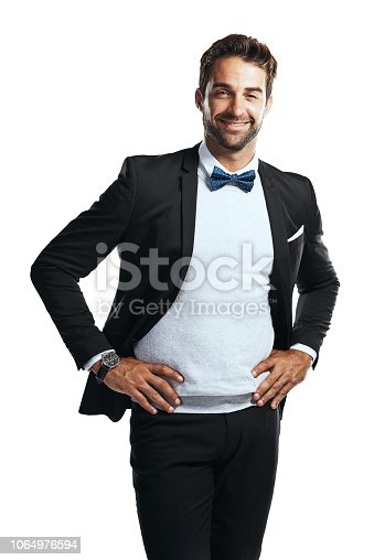 Studio shot of a handsome young man wearing a tuxedo against a white background
