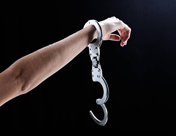 I'm free! Female hand wearing single, open handcuff. stock photo