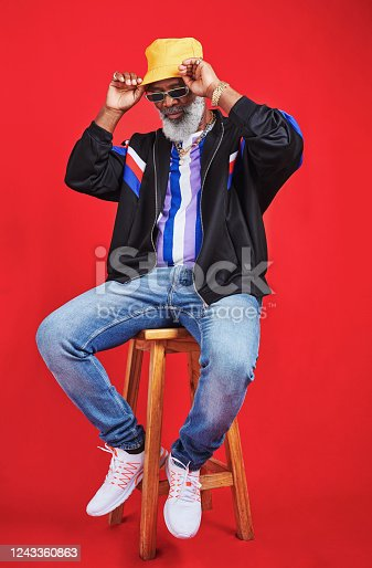 Studio shot of a senior man wearing retro attire while posing against a red background
