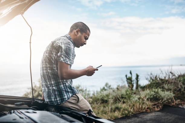 I'm glad I have roadside assistance Cropped shot of a young man with his broken down car on the side of a road aground stock pictures, royalty-free photos & images