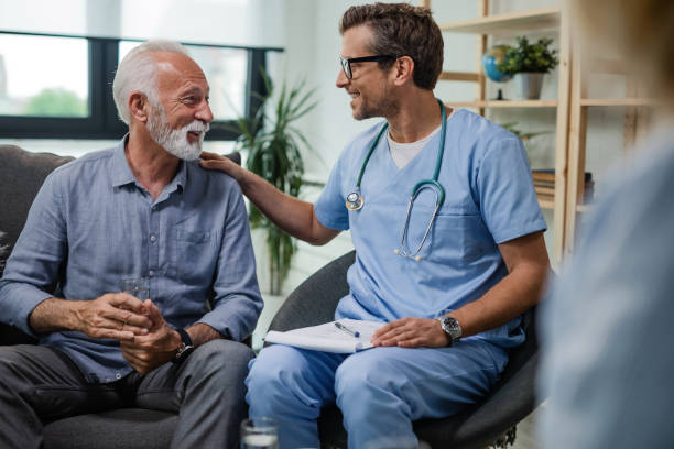 I'm glad to see you doing well! Happy doctor talking to senior male patient while being in a home visit. healthcare and medicine stock pictures, royalty-free photos & images