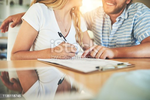 Shot of a young couple signing a document together at home