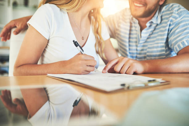 I'm glad we did this Shot of a young couple signing a document together at home diad stock pictures, royalty-free photos & images