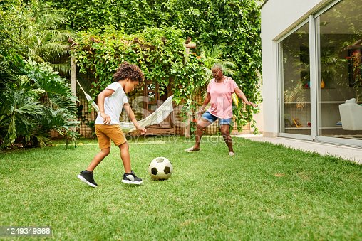 Shot of a little boy playing football with his grandmother in backyard