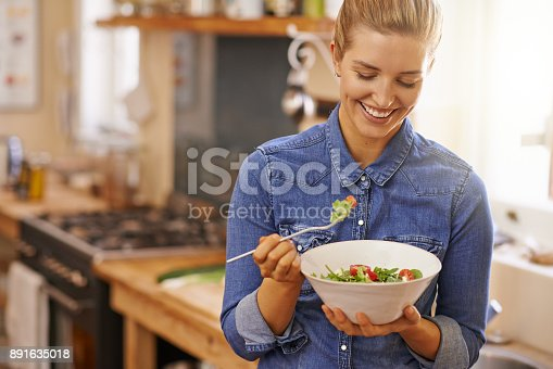 Shot of a beautiful young woman eating a healthy salad in her kitchen