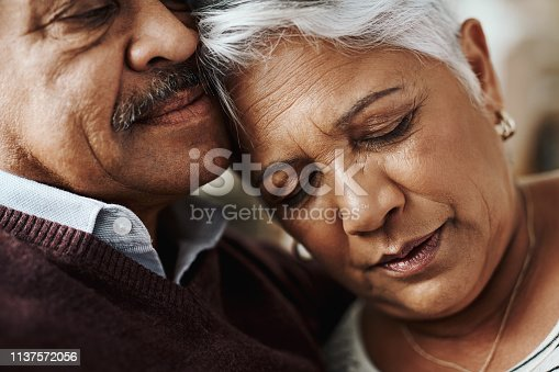 Closeup shot of a cheerful elderly couple seated on a couch together while holding each other at home during the day