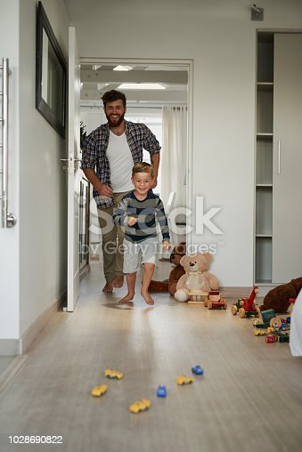 Full length shot of a handsome young man chasing his son around the house