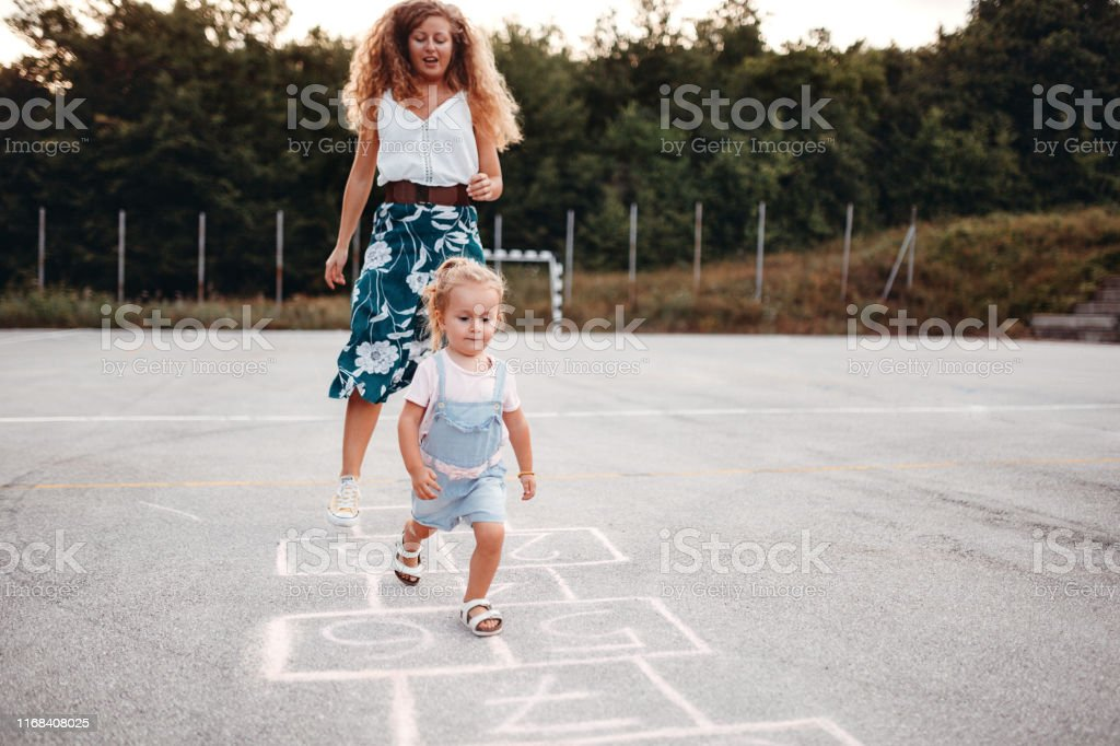 I'm gonna catch you Girl playing hopscotch in public park with her mother Adventure Stock Photo