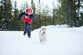 Shot of a boy playing with his pet husky dog in the snow outdoors on a cold winter day