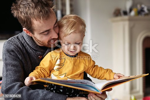 Cropped shot of an adorable little boy reading a book while sitting with his father at home
