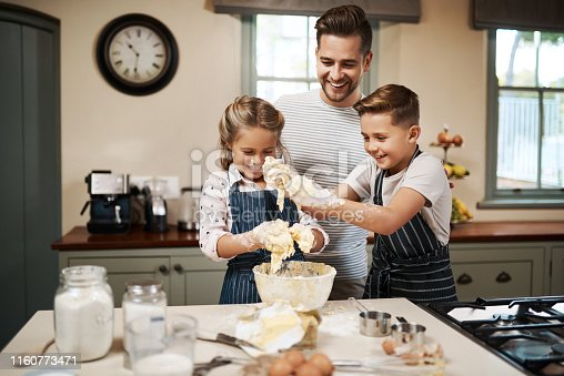 Shot of a man and his two children baking in the kitchen at home