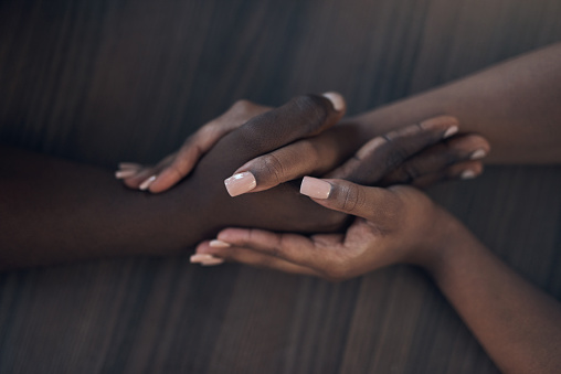 Cropped shot of an unrecognizable couple holding hands while at home during the day