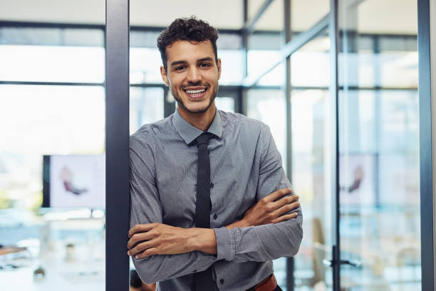 I'm here to make it happen Shot of a confident young businessman working in a modern office young adult stock pictures, royalty-free photos & images