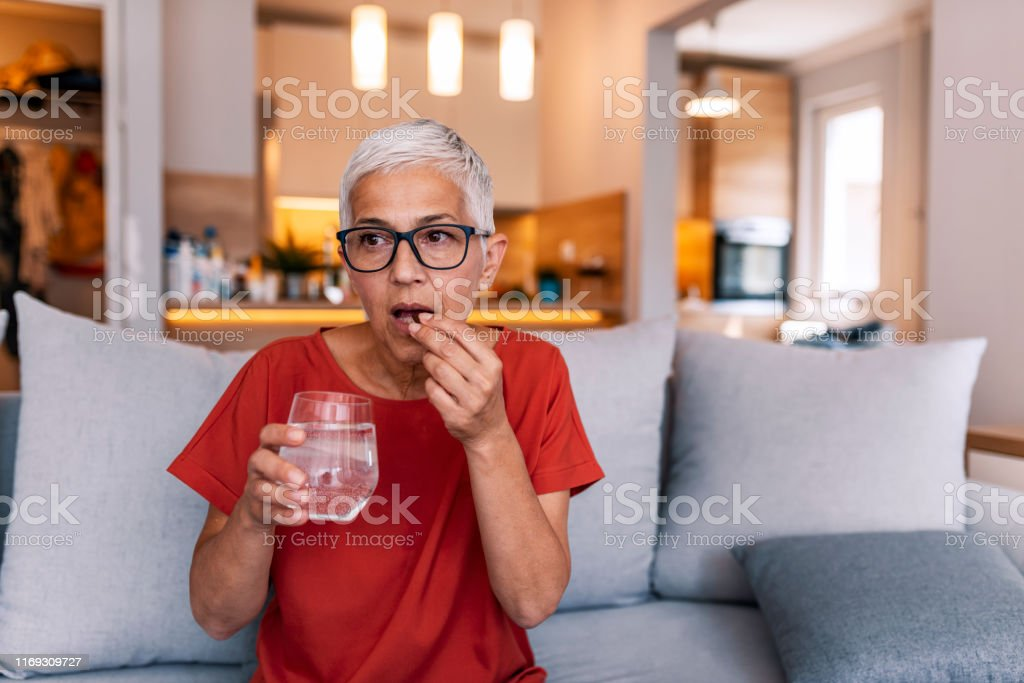 I'm hoping it works it's magic quickly Mature woman's morning routine - holding medicine and water. Photo of Mature woman with pill and glass of water at home. Mature woman sitting on bed, suffering from depression. Woman takes pill with omega-3 and holding a glass of fresh water. Adult Stock Photo