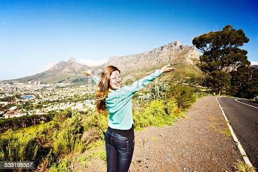 A beautiful young honey-blonde woman smiles widely as she looks over her shoulder, pointing out Table Mountain and Cape Town's City Bowl in front of her. A very happy tourist!