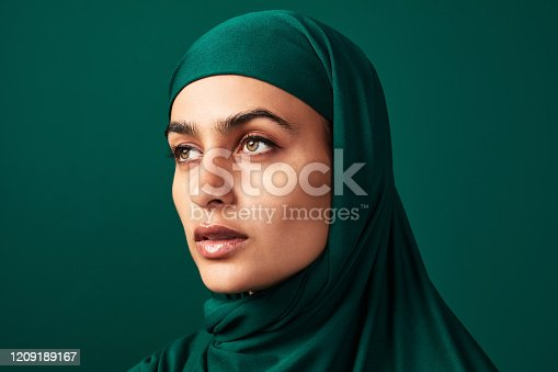 Cropped shot of a beautiful young woman wearing a headscarf against a green background