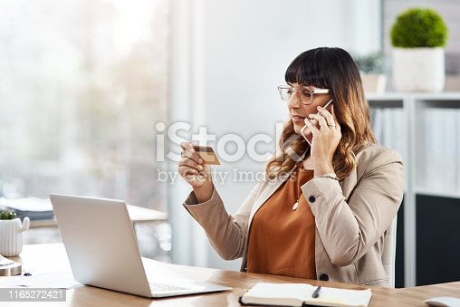 Shot of a beautiful young businesswoman holding her credit card and making a phone call in her office