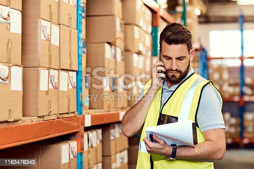 Shot of a young man talking on a cellphone while working in a warehouse