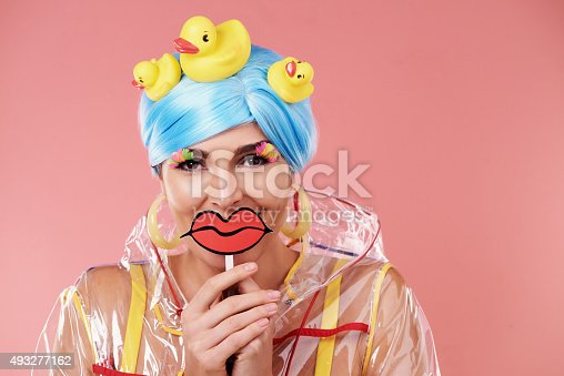 Shot of a retro-styled woman with rubber ducks in her blue hair holding cartoon lips in front of her mouthhttp://195.154.178.81/DATA/i_collage/pu/shoots/805731.jpg