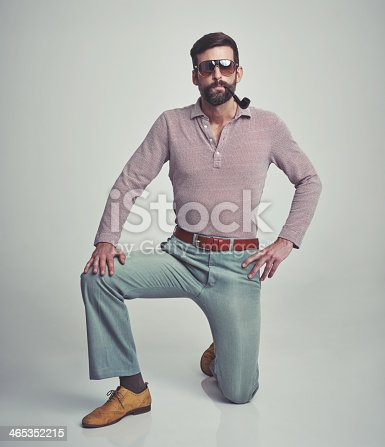 Studio shot of a handsome man striking a pose while wearing retro 70s style clothing