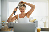 Mature woman does her hair by watching a tutorial on the internet at the time of the corona virus pandemic.