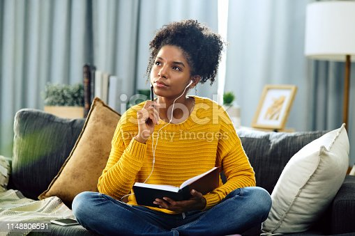 Shot of a young woman listening to music while writing in her notebook