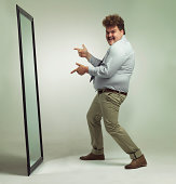 Shot of an excited overweight man celebrating while looking in a mirror
