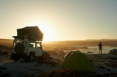 Shot of a silhouetted man admiring the view from his campsite by the sea