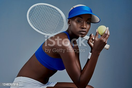 Studio shot of a sporty young woman posing with tennis equipment against a grey background