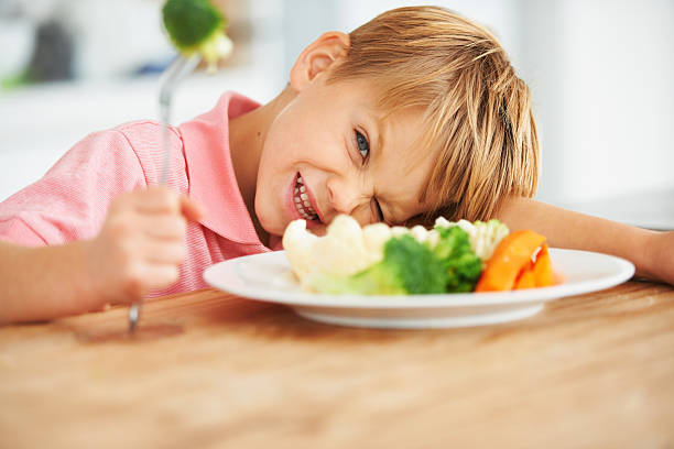 I'm not eating this! Portrait of a cute young boy looking naughty while holding a piece of broccoli on his fork using mouth stock pictures, royalty-free photos & images
