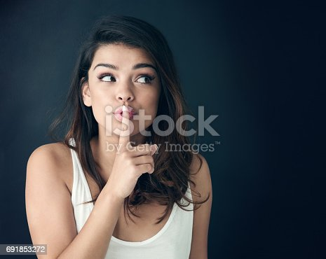 Studio shot of a beautiful young woman posing with her finger on her lips