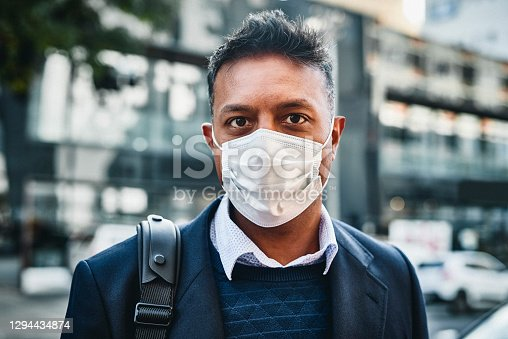Portrait of a businessman wearing a face mask against a city background