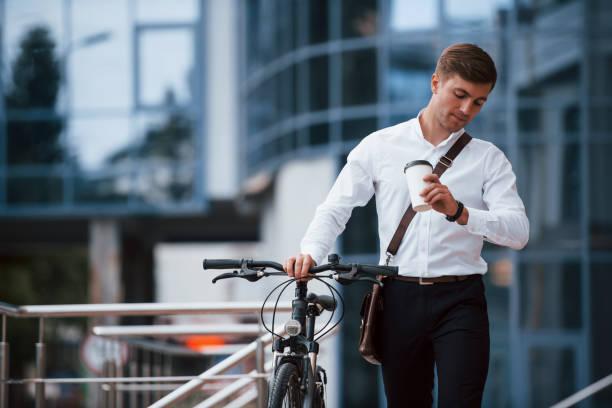 Ich werde nicht zu spät. Geschäftsmann in formeller Kleidung mit schwarzem Fahrrad ist in der Stadt – Foto