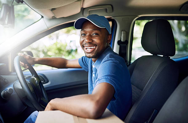I'm on my way Portrait of a young postal working sitting in his car during a delivery delivery man stock pictures, royalty-free photos & images