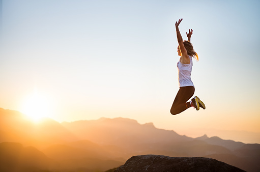 Shot of a woman jumping into the air enthusiastically while at the mountain